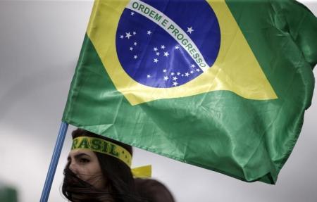 Una persona con una bandera de Brasil durante una protesta para que se haga efectivo el juicio político a la presidenta Dilma Rousseff, cerca del Congreso Nacional en Brasilia, Brasil, 13 de diciembre de 2015. Brasil sufrió el año pasado el deterioro más agudo en la percepción pública de corrupción, dijo el organismo de vigilancia Transparencia Internacional (TI) en su reporte anual publicado el miércoles que mostró que el abuso de poder sigue siendo generalizado a nivel mundial. REUTERS/Ueslei Marcelino