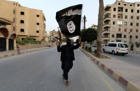 Un militante del Estado Islámico con una bandera de grupo en Raqqa el 29 de junio de 2014. Unas 3.500 personas, principalmente mujeres y niños, están retenidas y son tratadas como esclavos en Irak por militantes del grupo insurgente Estado Islámico que imponen duras normas marcadas por ejecuciones públicas, dijo Naciones Unidas el martes. REUTERS/Stringer