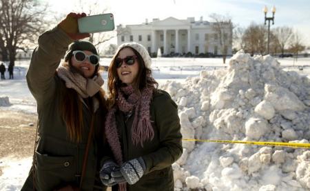 Unas turistas se toman una foto frente a la Casa Blanca, que está cubierta de nieve, en Washington. 25 de enero de 2016. Grandes ciudades de la costa este de Estados Unidos intentaban volver a la normalidad el lunes, luego que una poderosa tormenta dejó 60 centímetros de nieve en ciudades como Nueva York y Washington. REUTERS/Kevin Lamarque