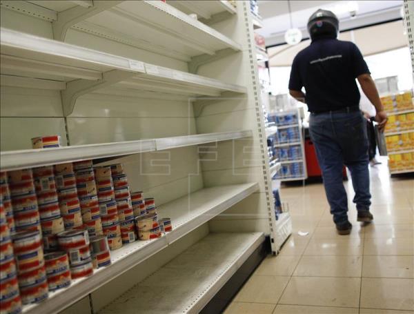 Un cliente recorre un pasillo con estanterías desabastecidas en un supermercado en Caracas (Venezuela), foto vía EFE